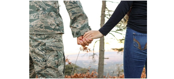 A person in an army uniform holding hands with a woman.